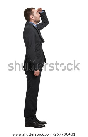 amazed businessman in black suit holding his hand on forehead and looking up into the distance. isolated on white background - stock photo