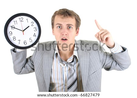 Amazed businessman in grey suit holding a clock over white