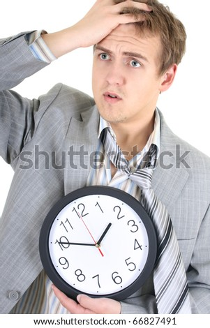 Amazed businessman in grey suit holding a clock over white - stock photo