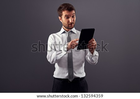 amazed businessman looking at tablet pc. studio shot over grey background