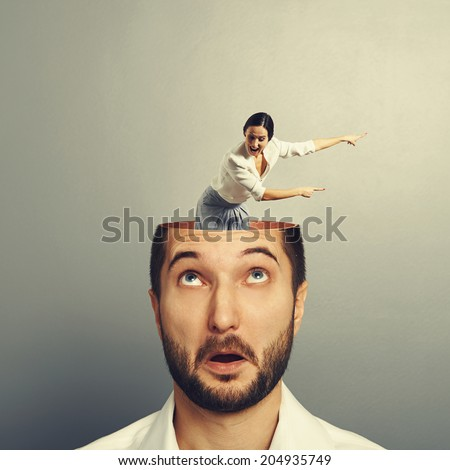 amazed businessman with open head. young screaming businesswoman standing into the head, looking at the man and showing the direction. photo over grey background - stock photo