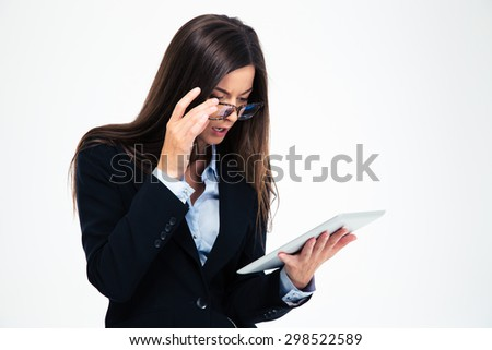 Amazed businesswoman in glasses looking on tablet computer isolated on a white background - stock photo