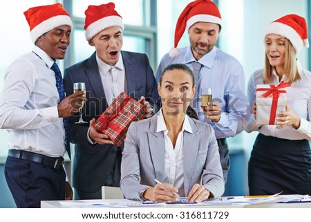 Amazed businesswoman looking at camera at workplace while colleagues with gifts and champagne congratulating her behind - stock photo