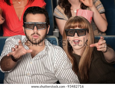Amazed Caucasian couple with 3D glasses in theater seats - stock photo