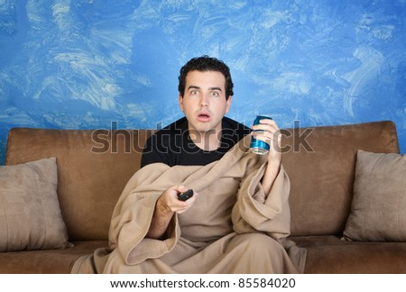 Amazed Caucasian man in bathrobe on sofa with can and remote control - stock photo