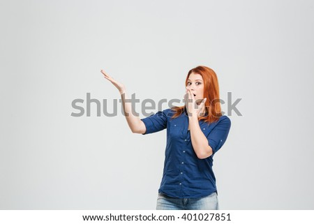 Amazed charming redhead young woman covered mouth with hand and showing copyspace over white background - stock photo