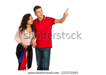 Amazed couple at shopping looking away and man pointing to copy space isolated on white background