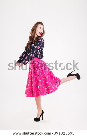 Amazed cute playful young woman in black high heels shoes  posing over white background - stock photo