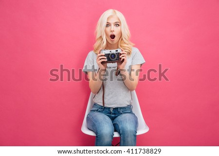 Amazed cute woman holding photo camera over pink background - stock photo