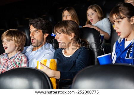 Amazed families watching movie in cinema theater - stock photo