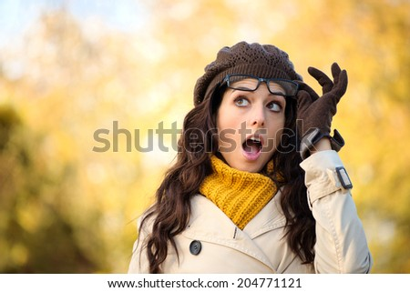 Amazed fashionable woman with mouth open looking surprised raising her glasses in autumn. Eye wear and fall season fashion concept. Beautiful female wearing raincoat, scarf, wool cap and gloves. - stock photo