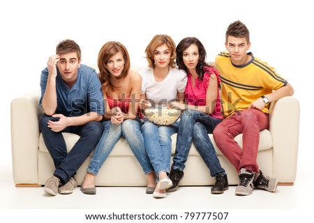 amazed friends sitting on couch watching movie with popcorn - stock photo