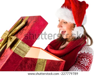 Amazed girl opening a magical christmas gift on white background