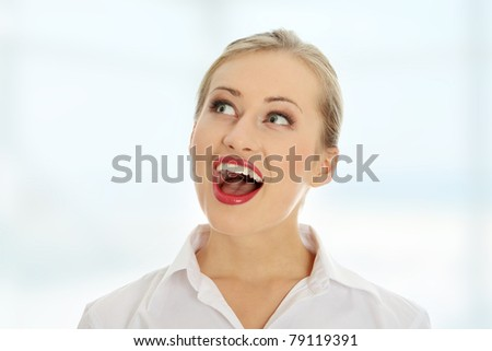Amazed happy business woman looking right - stock photo