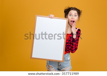Amazed happy young woman in checkered shirt and jeans shorts holding blank board over yellow background - stock photo