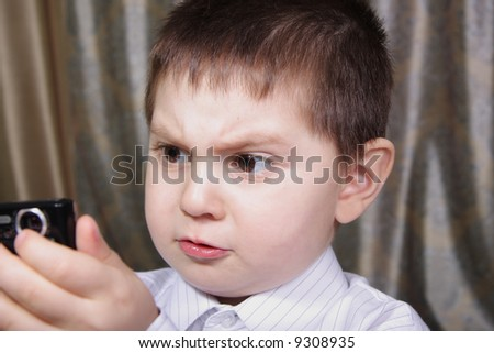 Amazed kid looking to result on camera focus on eyes