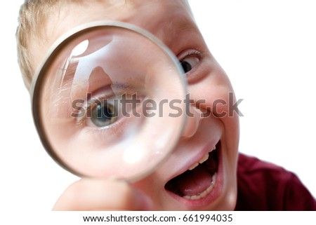 amazed kid watching through loupe (magnifier) with curiosity