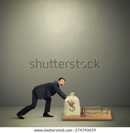 amazed man in formal wear reaching his hands to take bag with money in big mousetrap over dark grey background with empty copyspace overhead - stock photo