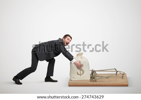 amazed man in formal wear reaching his hands to take bag with money in big mousetrap over light grey background - stock photo
