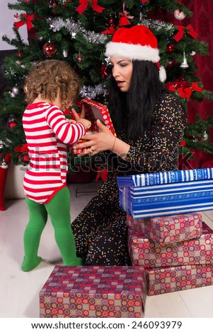 Amazed mother and toddler boy opening Christmas gifts under tree - stock photo