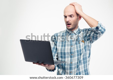 Amazed shocked young man in plaid shirt holding and using laptop over white background