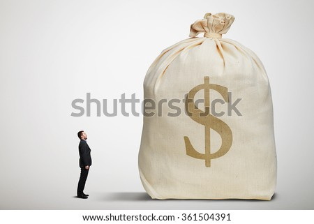 amazed small businessman with open mouth looking at big bag with money over light grey background