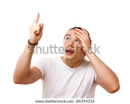Amazed smart man pointing up at copy space over white background - stock photo