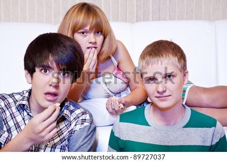 Amazed teens eat popcorn while watching movie - stock photo
