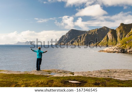 Amazed tourist enjoying views on the coast of fjord with stunning mountains on Lofoten islands in Norway - stock photo