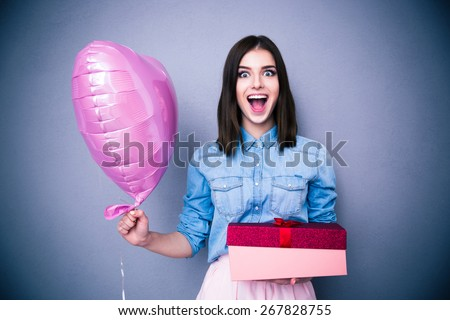 Amazed woman holding balloon and gift box over gray background. Looking at camera.  - stock photo