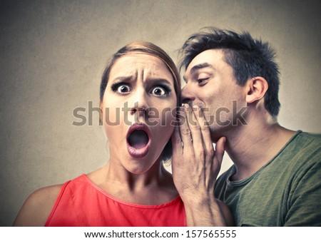 amazed woman listening gossip in the ear - stock photo