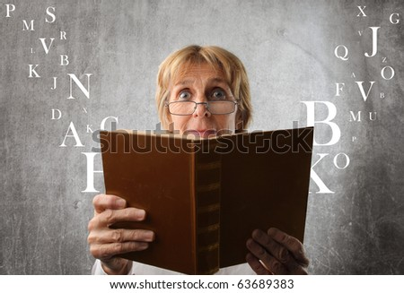 Amazed woman reading a book with letters flying away from it - stock photo
