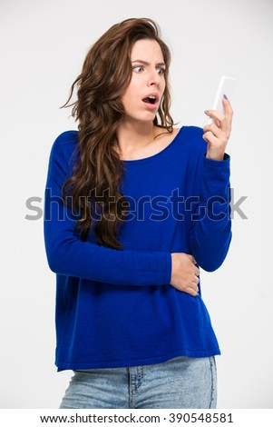Amazed woman reading message on smartphone isolated on a white background - stock photo