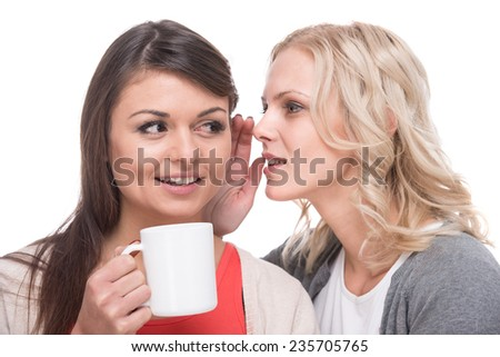 Amazed woman with a cup of coffee is listening gossip in the ear from another woman, on the white background. - stock photo