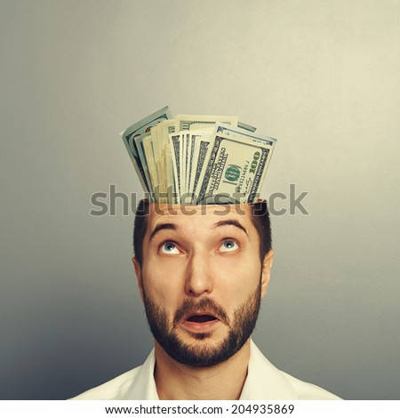 amazed young businessman with money in the head over grey background - stock photo