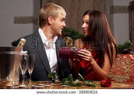 Amazed young lady is happy to get a christmas gift from her boyfriend - stock photo