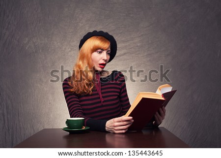 amazed young lady reading a exciting book on grunge background - stock photo
