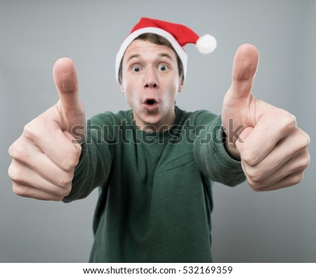 Amazed young man in christmas red hat with thumbs up on grey background