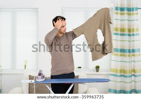 Amazed young man looking at burnt tshirt while standing by ironing board at home - stock photo