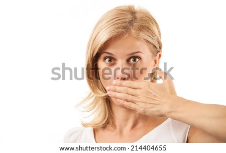 Amazed young woman covering mouth over background - stock photo