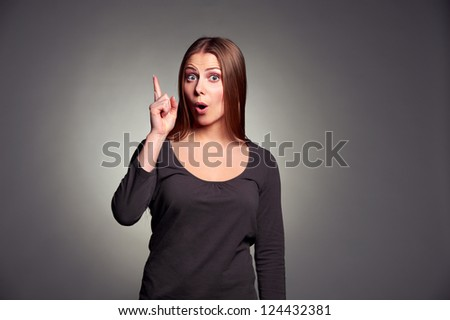 amazed young woman pointing up and looking at camera over dark background - stock photo
