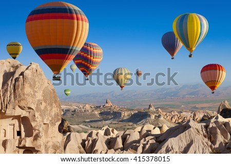 Amazing attraction - hot air balloons flying above unusual rocky landscape in Cappadocia, Turkey - stock photo