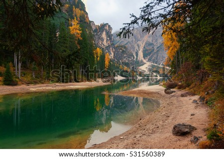 Amazing autumn scenery of Braies Lake (Lago di Braies) with colorful trees and mountains on background, Dolomite Alps, Italy.