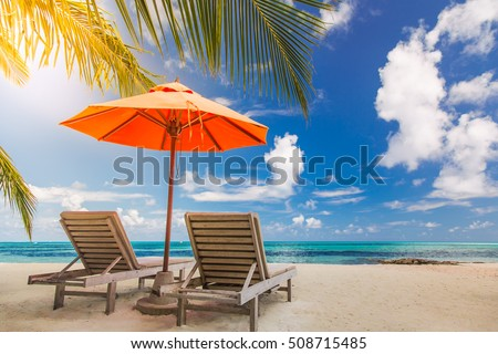 Amazing beach in Maldives. Relaxing blue sky and white sand. Wooden sun beds with sun umbrella. Inspirational luxury travel holiday background concept.