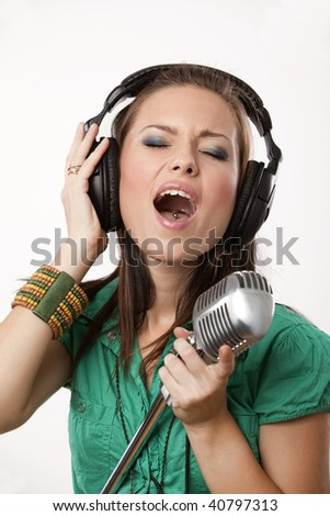 amazing beautiful girl with professional studio microphone and headphones on white background in studio shooting - stock photo