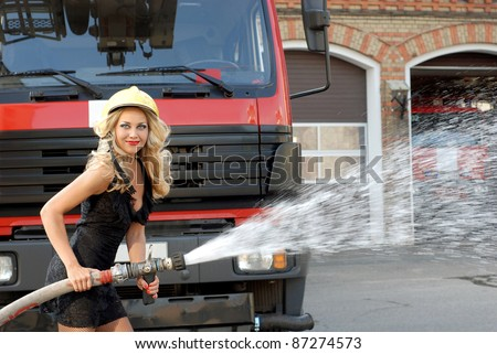 Amazing beautiful woman, holding a fire hose and wearing a helmet - stock photo