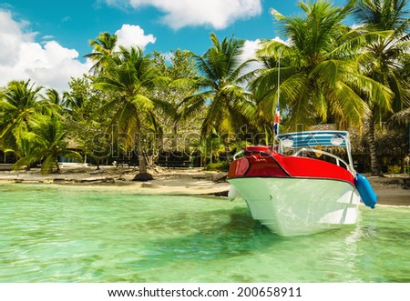 Amazing boat on sandy tropical Caribbean beach - stock photo