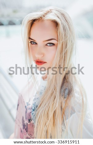 Amazing bright make-up model.Young sexy glamour blonde woman with perfect slim bode, wearing total warm white outfit,warm autumn jacket ,walking at the street, vintage colors, urban style. - stock photo
