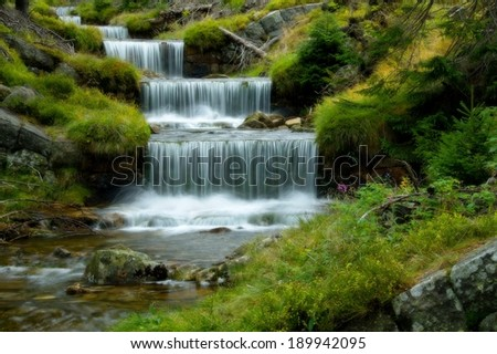 Amazing cascade in a wooded mountainous landscape  - stock photo