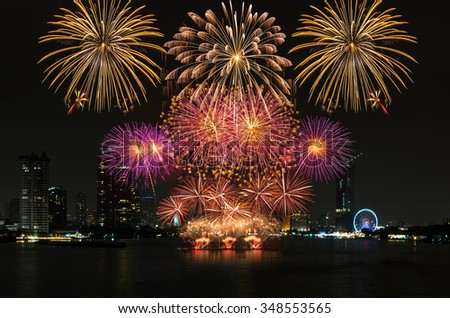 Amazing celebration fireworks over the river with bangkok cityscape soft focus background at night scene - stock photo